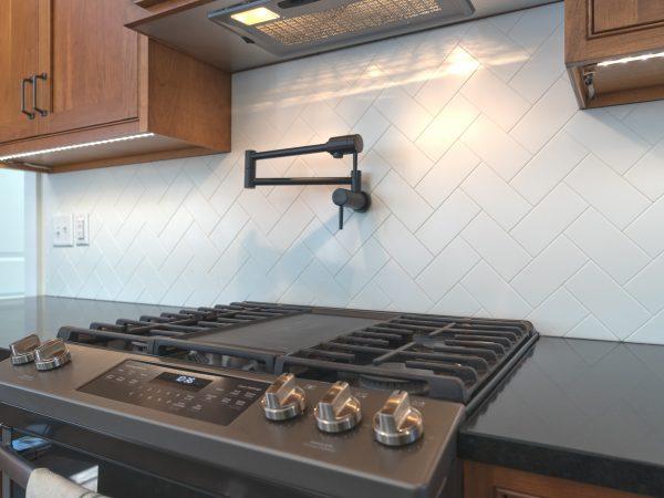 white tile black splash and black quartz countertop