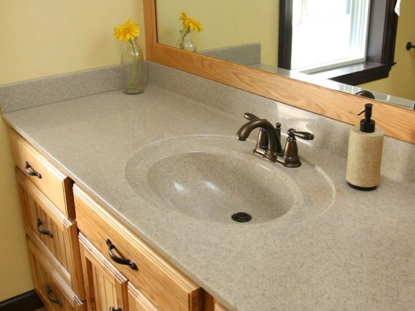 tan corian bathroom sink with wooden cabinets