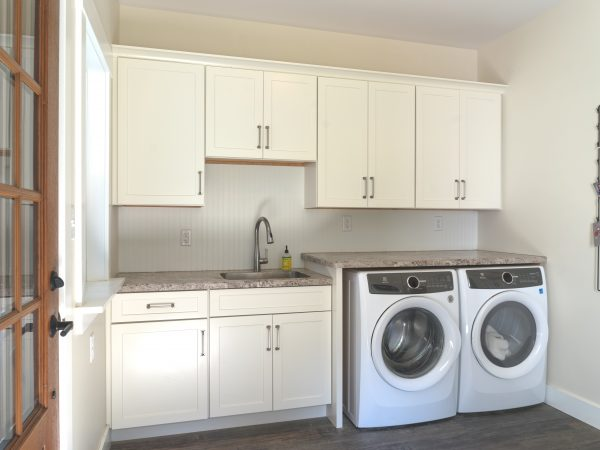 white kitchen cabinets in mudroom with marble sink