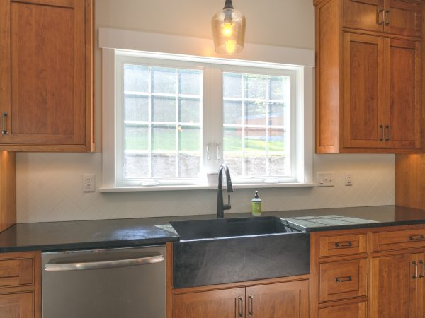 new wooden cabinets and countertop in farmhouse kitchen