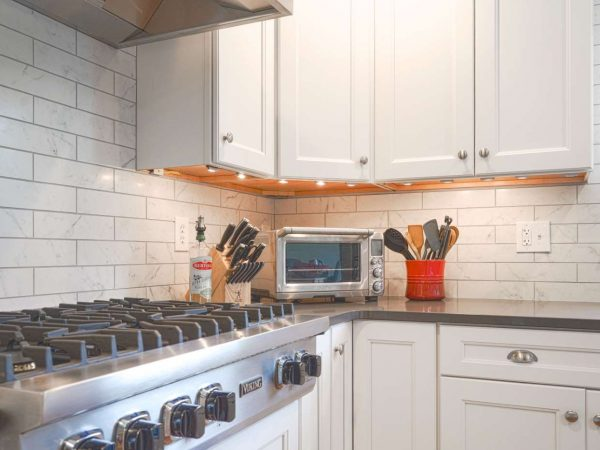 white kitchen cabinets with lights underneath