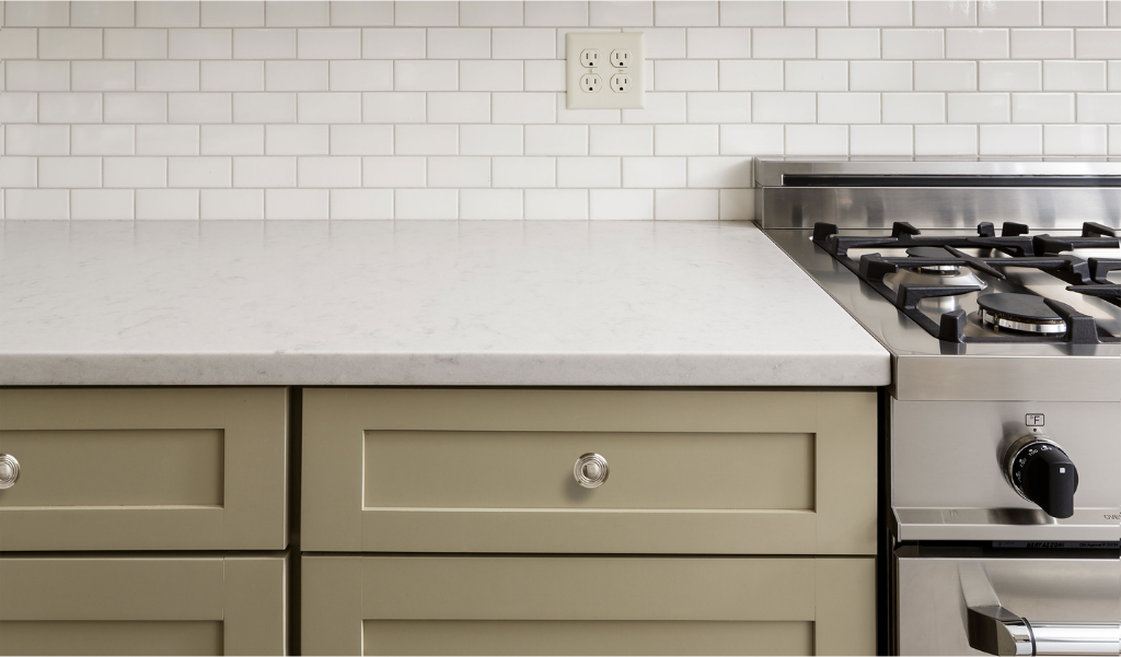 green kitchen drawers and quartz countertop